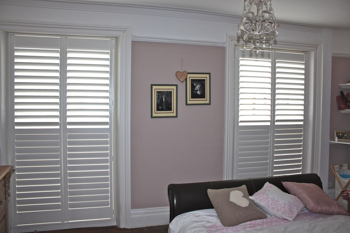 Two Sets Of Very Tall Shutters In A Bedroom