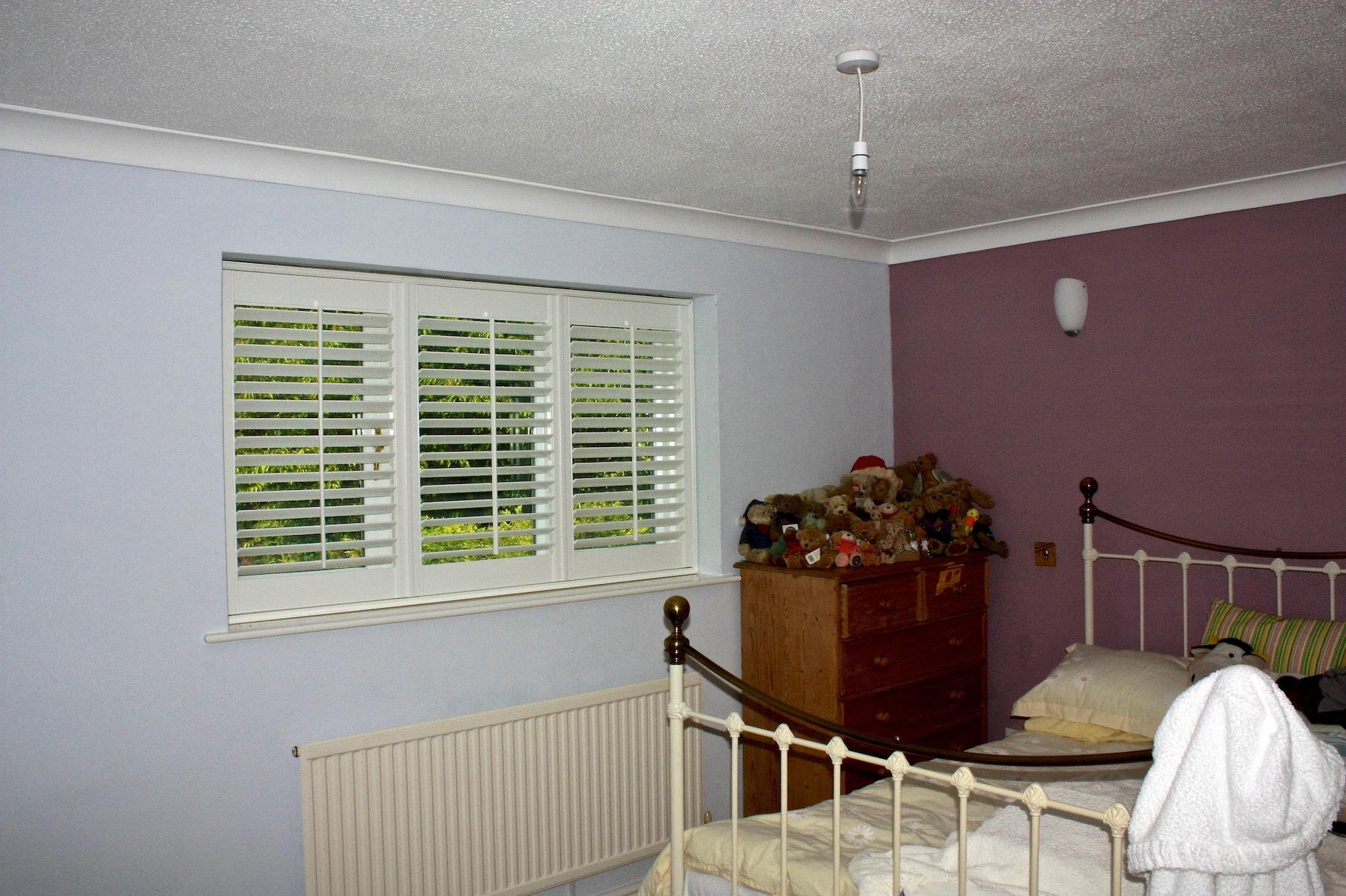 Shutters With Tilt Rods In A Bedroom
