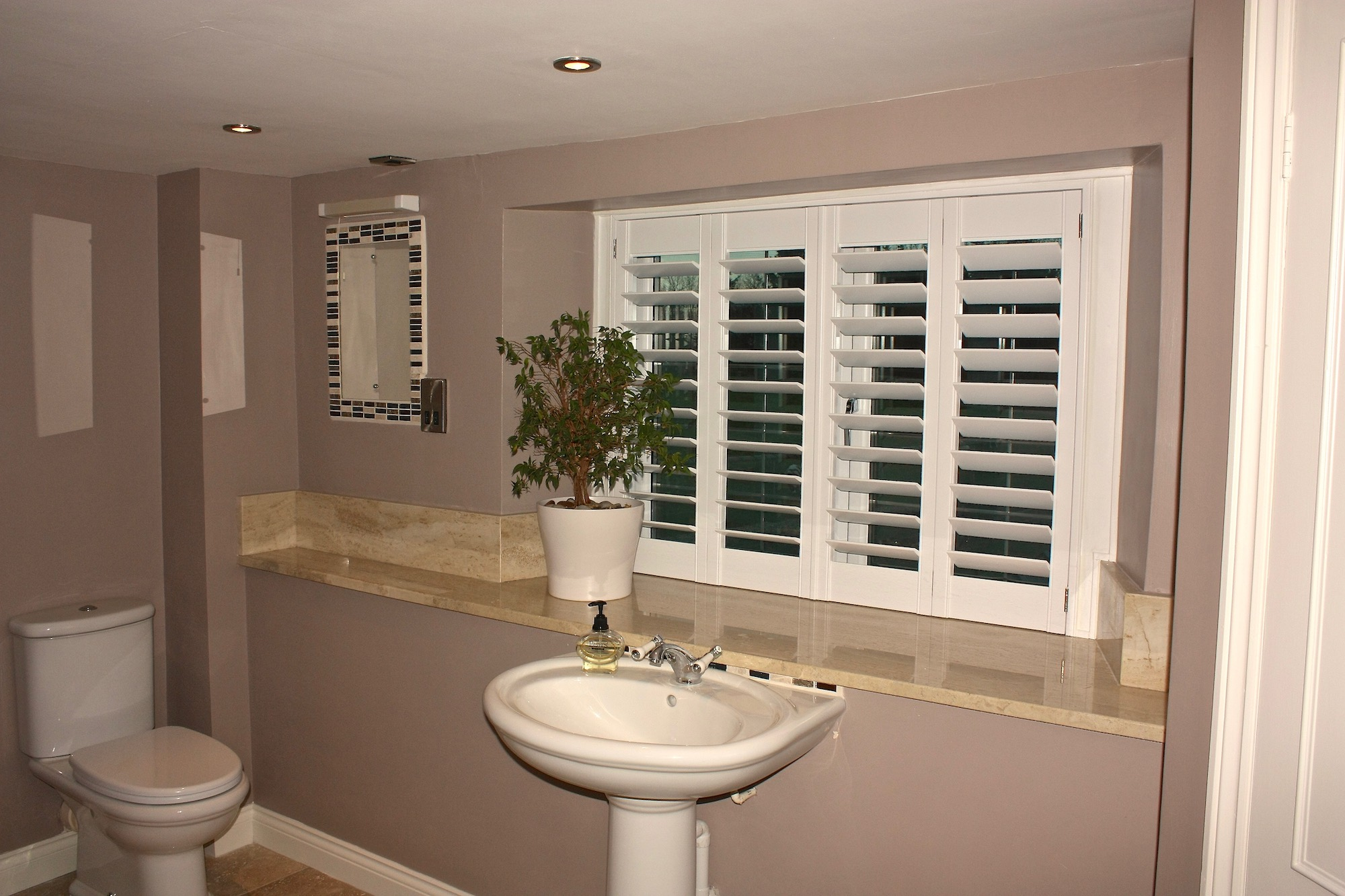 Plantation Shutters In A Marble Shower Room